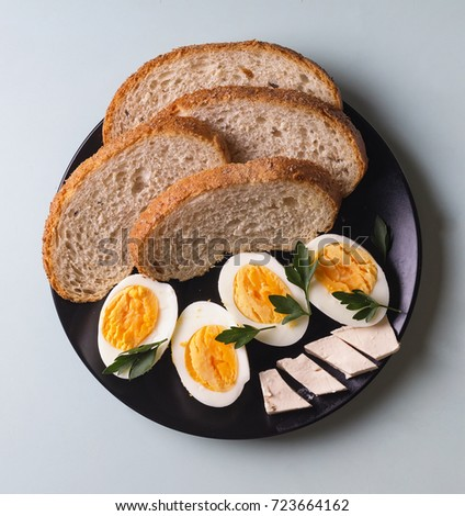 Style minimalism. Healthy breakfast. Boiled eggs, cereal bread and butter, parsley on a plate. Closeup, top view. #723664162