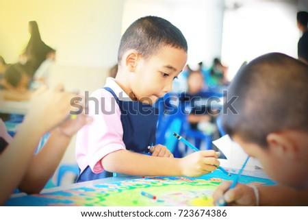 One Asian boy wearing a school uniform is painting. #723674386