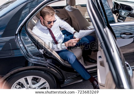 young stylish businessman in sunglasses with coffee and newspaper on backseat of car #723683269