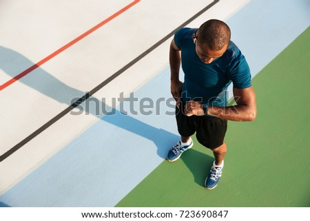 Top view of a young african sportsman looking at his wrist watch while standing on a track field Royalty-Free Stock Photo #723690847