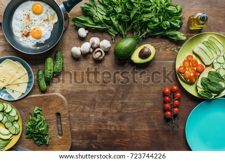 flat lay with fried eggs in frying pan, pieces of cheese on plate and fresh vegetables for cooking breakfast on tabletop #723744226
