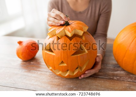 halloween, decoration and holidays concept - close up of woman with carved pumpkin or jack-o-lantern at home #723748696