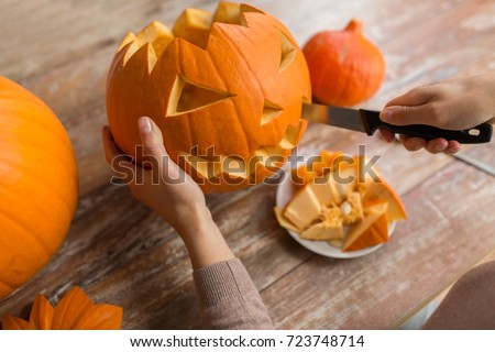 halloween, decoration and holidays concept - close up of woman with knife carving pumpkin or jack-o-lantern at home Royalty-Free Stock Photo #723748714