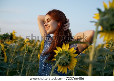 happy woman with closed eyes adjusts her hair in a field of sunflowers, a flowering of yellow flowers, nature                                #723766486