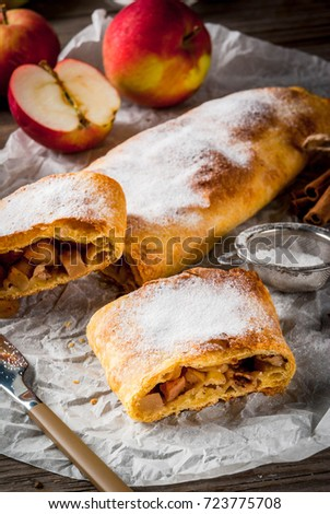 Home autumn, summer baking, puff pastries. Apple strudel with nuts, raisins, cinnamon and powdered sugar. On a wooden old rustic table. Sliced, with ingredients. Copy space #723775708