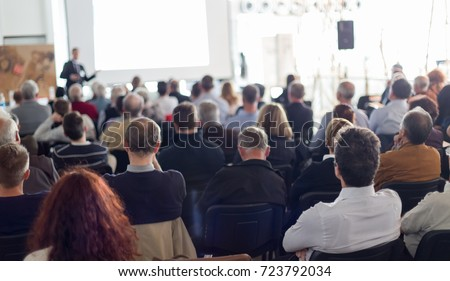 Speaker giving a talk in conference hall at business event. Audience at the conference hall. Business and Entrepreneurship concept. Focus on unrecognizable man in the audience. #723792034