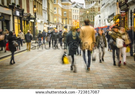 Man & women shopping on busy London high street with Christmas lights #723817087