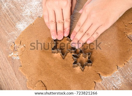 in the process of dealing with gingerbread start cookies,use star mold  cutting gingerbread dough on wooden table.  #723821266