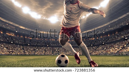 Soccer player kicks the ball on the soccer stadium. He wear unbranded sports clothes. Stadium and crowd made in 3D. #723881356