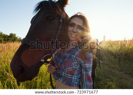 Woman and horse in the meadow at summer evening, horizontal #723971677