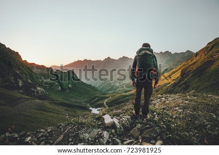 Man hiking at sunset mountains with heavy backpack Travel Lifestyle wanderlust adventure concept summer vacations outdoor alone into the wild Royalty-Free Stock Photo #723981925