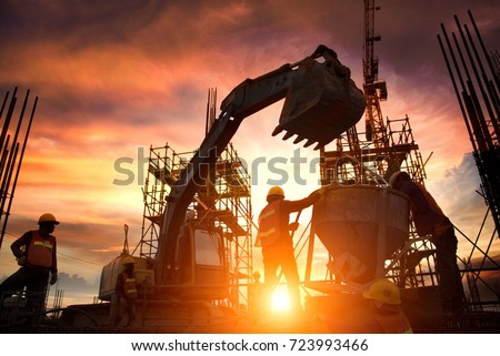Silhouette Teams of Business Engineers looking for blueprints in construction sites through blurry construction sites at sunset. Royalty-Free Stock Photo #723993466