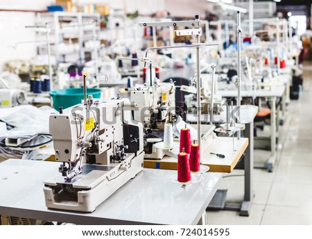 Interior of garment factory shop. Closes making atelier with several sewing machines. Tailoring industry, fashion designer workshop, industry concept Royalty-Free Stock Photo #724014595