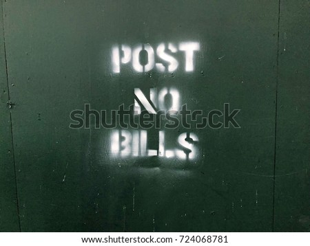 Construction zone Post No Bills spray painted on green wall in New York City