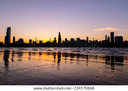 Chicago skyline picture during beautiful orange yellow sun as it lowers below the building silhouettes and reflections in the water of lake Michigan in the foreground