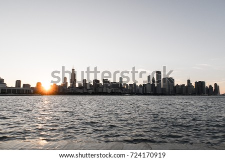 Chicago skyline picture during beautiful sunset with building silhouettes and rippling waves of Lake Michigan water in the foreground