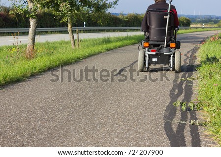 motor-driven wheel chair on a street in september fall season and sunny weather condition in south germany countryside near city of stuttgart #724207900