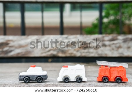 toy model of police car, ambulance van and electricity and utility service truck for kid on wooden floor