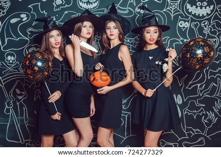 Beautiful girls in witches costumes on a dark background with a picture. Halloween. #724277329