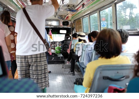 People holding on asia local bus. A bus is a road vehicle designed to carry many passengers. Buses can have a capacity as high as 300 passengers. #724397236