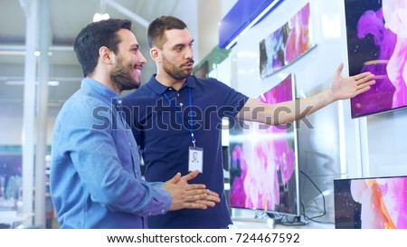 In the Electronics Store Professional Consultant Shows Latest 4K UHD TV's to a Young Man, They Talk about Specifications and What Model is Best for Young Man's Home. Store is Bright. Royalty-Free Stock Photo #724467592