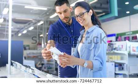 In the Electronics Store Consultant Gives Professional Advice to a Young Woman, She Considers Buying New Tablet Computer and Needs Expert Opinion. Store is Modern, Bright and Has all the New Devices. Royalty-Free Stock Photo #724467712