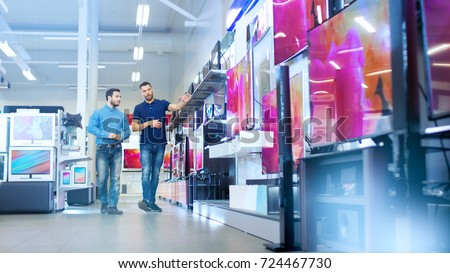 In the Electronics Store Professional Consultant Shows Latest 4K UHD TV's to a Young Man, They Talk about Specifications and What Model is Best for Young Man's Home. Store is Bright. Royalty-Free Stock Photo #724467730