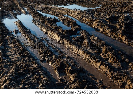 Mud and puddles on the dirt road. #724532038