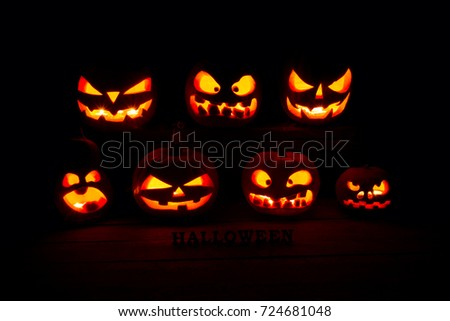 The concept of Halloween. A lot of Evil scary pumpkin in the dark. Jack Lantern in the darkness with Halloween inscription #724681048