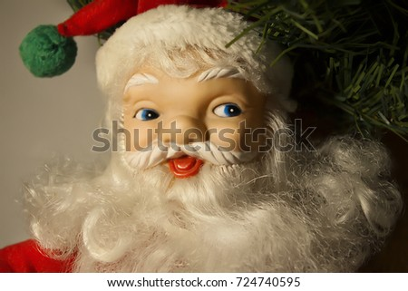 New Year's Christmas soft toy figure smiling Santa Claus under the Christmas tree close up