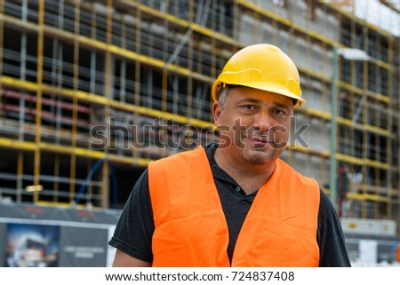 Civil engineer wearing safety protective wear posing against scaffolding #724837408