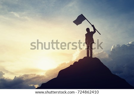 Silhouette of businessman hold a flag on top mountain, sky and sun light background. Vintage filter. Business, success, leadership, achievement and people concept. Royalty-Free Stock Photo #724862410