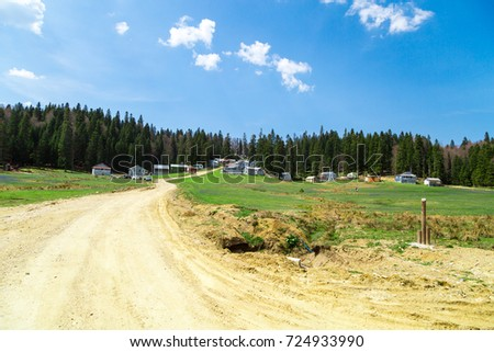 General view of Purenli Plateau with mountain houses in meadow area and big pine trees around on bright sky background. #724933990