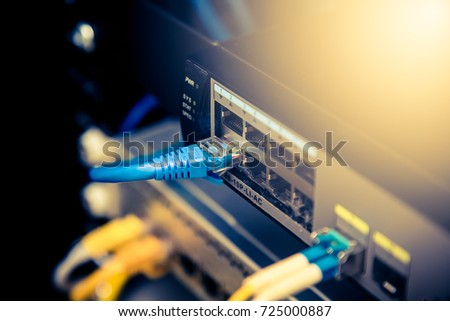Network cables connected in a technology data center. Royalty-Free Stock Photo #725000887