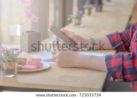 Close Up businessmen working at a coffee shop with a document with a smartphone and a laptop computer. #725033734