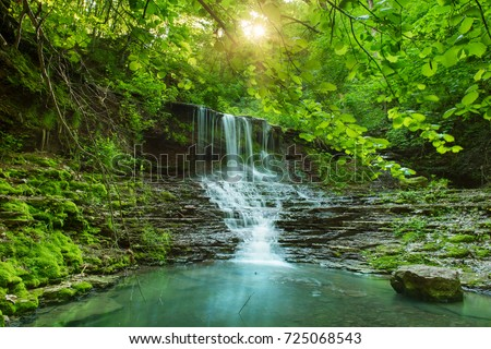 Beautiful mountain rainforest waterfall with fast flowing water and rocks, long exposure. Natural seasonal travel outdoor background with sun shihing #725068543
