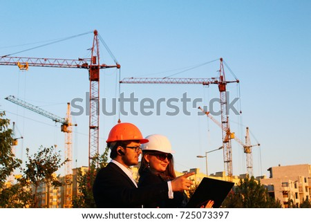 male and female in the helmets on the background of the building #725073397