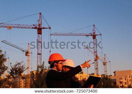 male and female in the helmets on the background of the building #725073400