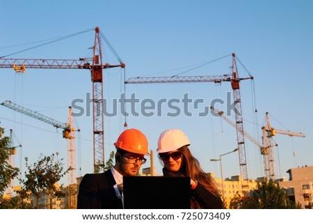 male and female in the helmets on the background of the building #725073409