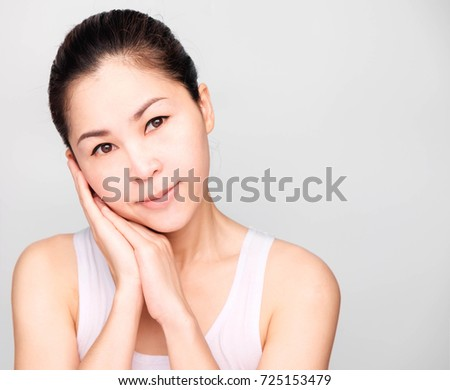 closeup beautiful young asian woman face,Two hands touch the side of the cheeks.isolated on gray background #725153479