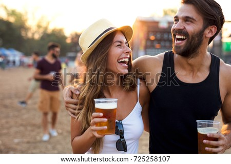 Young and cheerful couple in music festival. Royalty-Free Stock Photo #725258107