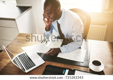 Smiling young African business executive talking to a client on his cellphone while sitting at his desk in an office #725283343