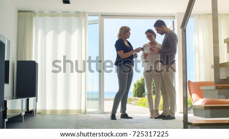 Professional Real Estate Agent Shows Stylish Modern House to a Beautiful Young Couple Who are in the Market for Purchasing/ Renting New Home. House Has Floor to Ceiling Windows and Seaside View. #725317225