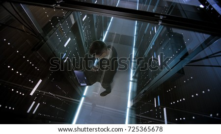 Top View Through the Glass of IT Engineer Working with Laptop in Data Center Full of  Active Rack Servers. Royalty-Free Stock Photo #725365678