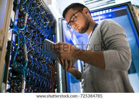 Low angle  portrait of young man using digital tablet standing by server cabinet while working with supercomputer in blue light Royalty-Free Stock Photo #725384785
