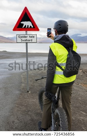 Teen boy riding a fatbike and taking picture of a polar bear warning sign with his mobile phone in Svalbard. Sign located at the end of Longyearbyen.Translation of text: Applies to all of Svalbard