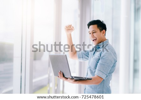 Happy excited Asian man holding laptop and raising his arm up to celebrate success or achievement. #725478601
