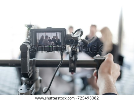 Videographer using steadycam, making video of business people at meeting