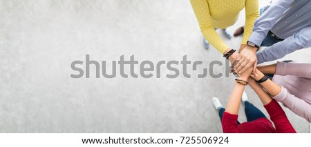 Close up top view of young business people putting their hands together. Stack of hands. Unity and teamwork concept. Royalty-Free Stock Photo #725506924