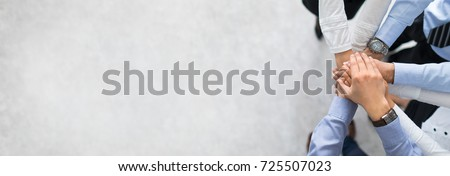Close up top view of young business people putting their hands together. Stack of hands. Unity and teamwork concept. Royalty-Free Stock Photo #725507023